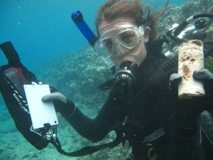 Steph Duce showing a coral core underwater in Tahiti